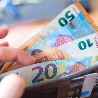 ARCHIV - 04.12.2018, Sachsen, Dresden: ILLUSTRATION - Eine Frau hält eine Geldbörse mit zahlreichen Banknoten in der Hand (gestellte Szene). (zu dpa Pensionskassen unter Druck: Aufsicht greift ein vom 06.12.2018) Foto: Monika Skolimowska/ZB/dpa +++ dpa-Bildfunk +++