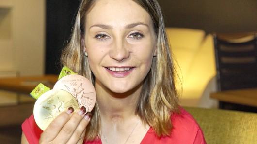 Olympiasiegerin Kristina Vogel zeigt stolz ihre Gold- und Bronzemedaille.
