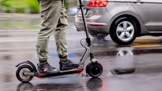 Ein Mann fährt mit einem E-Scooter auf der Straße (Symbolbild).