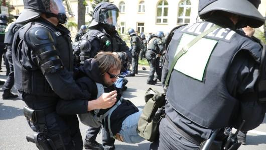 Erfurt: Polizeibeamte lösen eine Sitzblockade auf einer Straße auf und tragen Demonstranten weg. Sie wollten eine Demonstration der AfD verhindern.