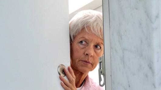 Eine ängstliche alte Frau öffnet Wohnungstür.