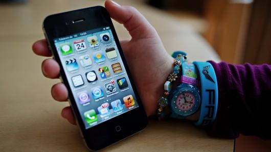 Ein junges Mädchen hält ein iPhone in der Hand.