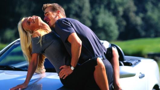 Ein Verliebtes Paar amüsiert sich auf der Motorhaube.