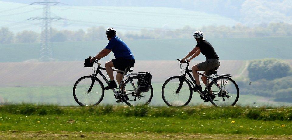 Zwei Fahrradfahrer fahren bei Sonnenschein am 22.04.2011 auf einer Straße durch das Altenburger Land bei Göpfersdorf.