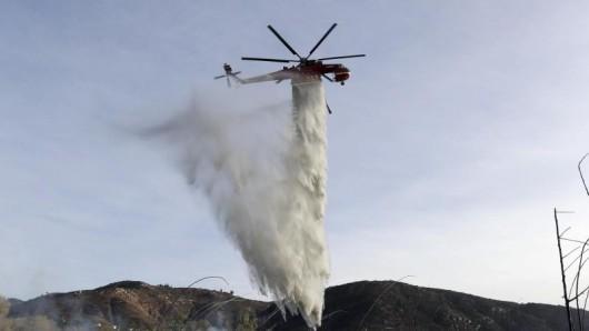Ein Löschhubschrauber wirft seine Wasserladung über einem Schwelbrand von Holzschnitzeln und Mulch ab.