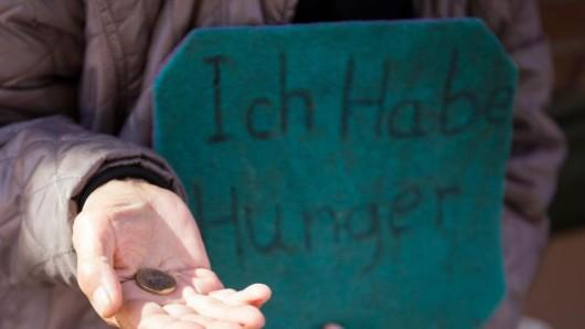 Eine Frau bittet in Hamburg mit einem Schild mit der Aufschrift Ich habe Hunger um Spenden.
