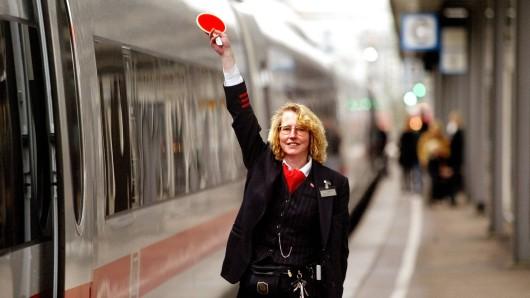 Eine Schaffnerin der Deutschen Bahn winkt mit der klassischen Kelle. Die Bahn sucht für die neue Kollegen - auch in Thüringen. (Archivbild)