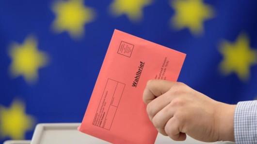 Ein Wahlbrief zur Europa-Wahl wird in eine Wahlurne eingeworfen.
