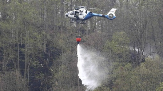 Ein Polizeihubschrauber löscht einen Brand im Wald an der Bleilochtalsperre. Der Brand am Heinrichstein bei Saalburg-Ebersdorf im Saale-Orla-Kreis ist erneut ausgebrochen.