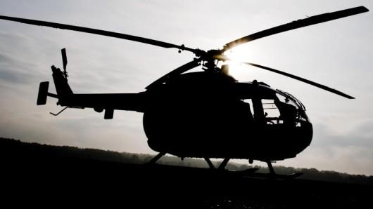 Umriss eines Mannes neben einem Hubschrauber der Bundeswehr.