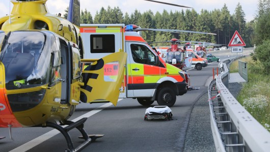 Rettungshubschrauber und Krankenwagen stehen am 03.07.2017 auf der Autobahn A9 bei Münchberg (Bayern). Nach ersten Informationen soll ein Reisebus nach einem Zusammenstoß mit einem Lastwagen in Brand geraten sein. (zu dpa Wohl Tote in brennendem Reisebus - mindestens 31 Verletzte am 03.07.2017)