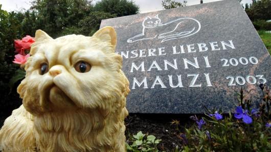 Eine Plastikkatze sitzt vor einem Grab. In Jena sollen demnächst Bestattungen von Menschen und Tieren in einem Grab zulässig sein. (Symbolfoto)