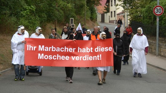 Mit einem Plakat «Ihr Marbacher habt diese Moschee verdient» ziehen Gegner des umstrittenen Moscheebaus in Erfurt-Marbach durch den Ortsteil der Landeshauptstadt.