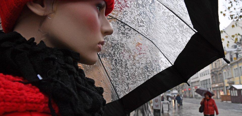 Thüringen, Erfurt: Eine Schaufensterpuppe steht vor einem Bekleidungsgeschäft in der Einkaufsstraße Anger, während Schneeregen auf den Schirm fällt.