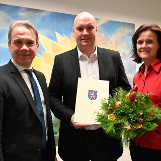 Innenminister Georg Maier spricht Steffen Grimm die Belobigung im Beisein von Antje Hochwind, Landrätin des Kyffhäuserkreises, aus.