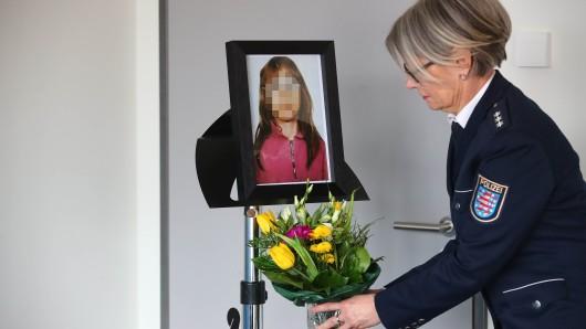 Eine Beamtin der Polizei Jena stellt einen Blumenstrauß unter das Foto der ermordeten Stephanie vor einer Pressekonferenz.