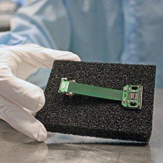 Im Bild zu sehen ist der im Leibniz-Institut für Photonische Technologien (Leibniz-IPHT) Jena gefertigte Thermosensor, präsentiert von einem Mitarbeiter der Abteilung Quantendetektion, in der der Sensor entwickelt wurde. Es handelt sich um den kleinen schwarzen Chip, im Bild rechts zu erkennen (zwischen den beiden ovalen Aussparungen). Er ist 0,5mm x 5 mm x 8 mm groß und wiegt ca. 50 Milligramm.