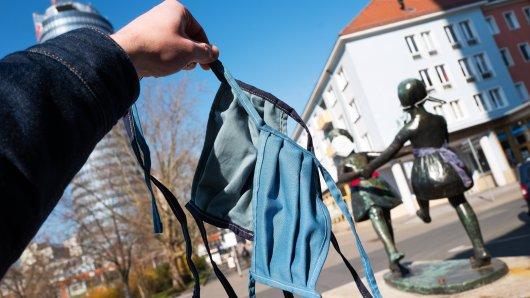 Zwei handgenähte Masken für die Maskenpflicht in Jena. Im Hintergrund der JenTower und die Statue der beiden tanzenden Mädchen, die Unbekannte mit Atemmasken versehen haben.