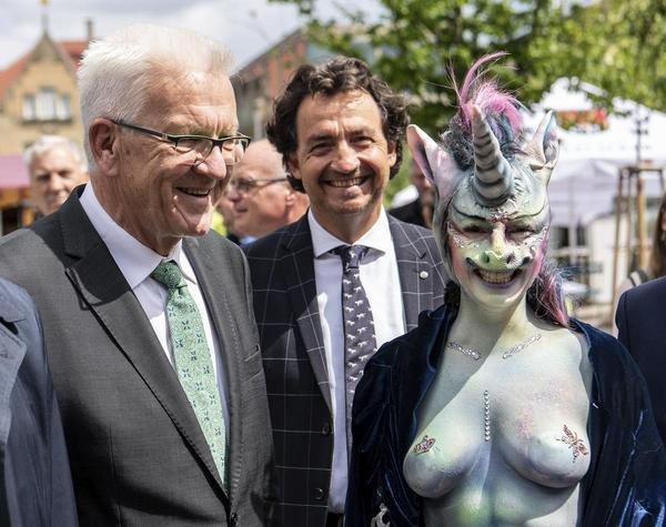 Winfried Kretschmann, Ministerpräsident von Baden-Württemberg (Die Grünen), neben einer bemalten Frau im Einhornoutfit - darunter verbirgt sich die Stadträtin von Schwäbisch Gmünd, Cynthia Schneider (Die Linke).