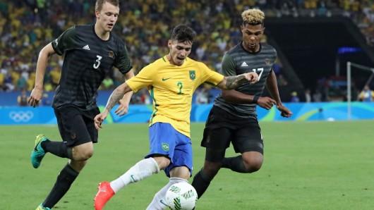 Zeca von Brasilien (m.) kämpft mit Lukas Klostermann (l.) und Serge Gnabry (r.) von Deutschland um den Ball.