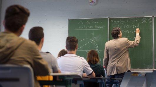 Ein Lehrer schreibt Mathe-Aufgaben an eine Tafel.