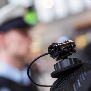 Ein Polizeibeamter trägt eine Body-Cam auf seiner Schulter.