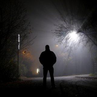 Ein Mann ist nachts alleine auf einer Straße unterwegs.
