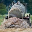 Ein Bauer bringt Gülle aus auf einem Feld.