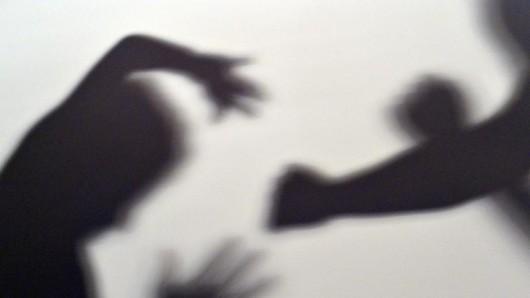 Illustration: Person schlägt mit Faust auf andere Person ein.