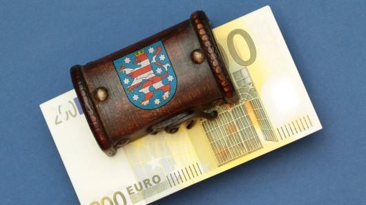 Landeshaushalt und Steuereinnahmen: Bündel 200 Euro Geldscheine liegen in einer Schatztruhe mit Landeswappen des Flächenlands Thüringen