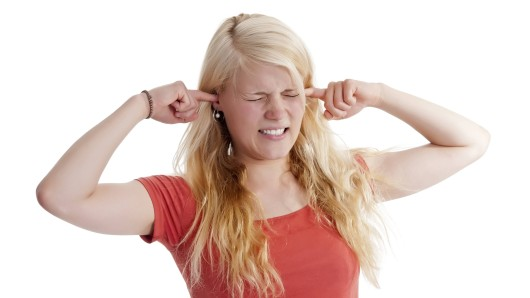 Eine junge Frau hält sich die Ohren zu. (Symbolfoto)