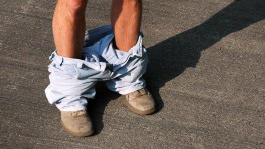 Ein Mann hat seine Hosen heruntergelassen.