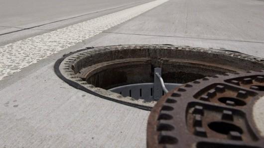 Offener Gullydeckel und letzte Ausbesserungen beim Ausbau der Autobahn.
