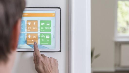 Eine Frau benutzt eine Smart Home-Kontrollstelle in ihrer Wohnung.