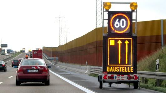 Mobiles Baustellen-Warnschild auf der Autobahn A 3 Ein mobiles Warnschild auf dem Standstreifen der Autobahn A3 warnt vor einer Baustelle und zeigt eine Geschwindigkeitsbegrenzung von 60 km/h an. An der Autobahnbaustelle verringert sich die Fahrbahn von 3 auf 2 Spuren. , Rheinland-Pfalz, Deutschland, 09.10.2003