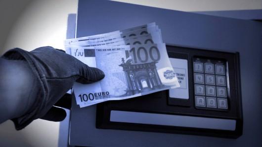 Dieb stiehlt Geld aus einem Wandtresor.