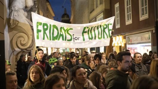 Österreich, Graz: Teilnehmer einer Fridays for Future-Klimademonstration unter dem Motto Lichtermeer fürs Klima ziehen mit einem Plakat durch die Stadt. Weltweit werden an diesem Tag mehr als 1650 Demonstrationen in rund 100 Staaten erwartet.