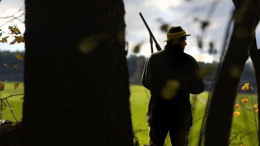 Ein Jäger steht am Waldrand.
