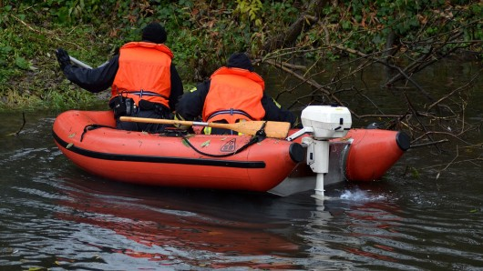 Polizisten suchen auch mit einem Schlauchboot auf der Werra bei Bad Salzungen nach einem vermissten einjährigen Jungen.