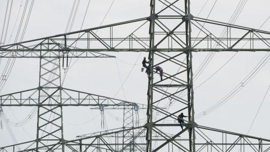 Arbeiter stehen bei Wartungsarbeiten auf einem Freileitungsmast der Südwestkuppelleitung.
