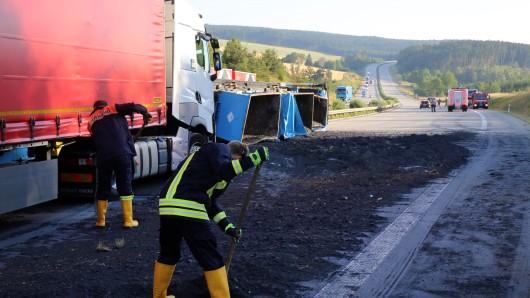 Feuerwehrleute arbeiten auf der Autobahn 9 bei einer Unfallstelle, an der ein Lastwagen mit einem Anhänger ungekippt ist.