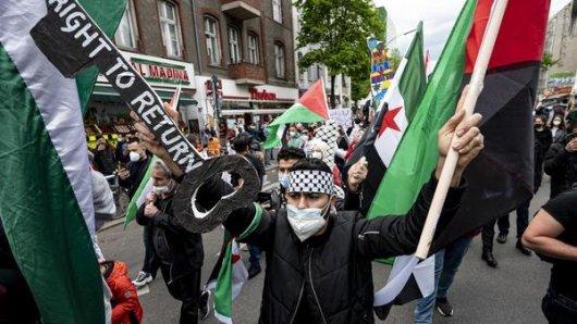 Ein Teilnehmer der Demonstration verschiedener palästinensischer Gruppen läuft und einem großen Schlüssel mit der Aufschrift Right to Return durch Neukölln.