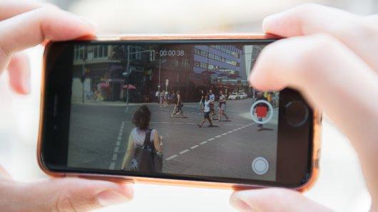 Ein Mann filmt eine Straße in Berlin mit seinem Handy.