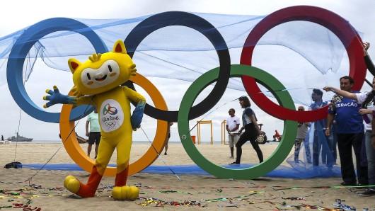 Vinicius ist das Maskottchen der olympischen Spiele 2016 in Rio. Es steht vor den Olympischen Ringen.
