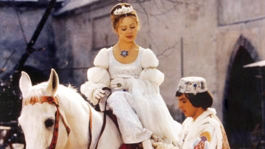 Der Prinz (Pavel Travnicek) passt Aschenbrödel (Libuse Safrankova) im Film Drei Haselnüsse für Aschenbrödel den verlorenen Schuh an. (undatierte Filmszene)